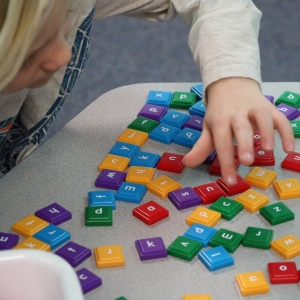 student playing with letter tiles